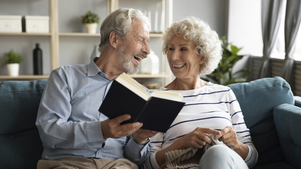 70s spouses feels happy spend time together at home doing favorite hobby, wife holds needles knitting husband hold book discuss with beloved woman interesting literature, retired life pastime concept